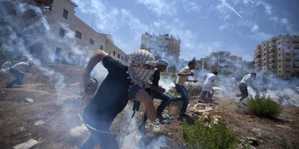 Palestinier demonstrerar mot Gaza-kriget i augusti 2014, ochblir bemöttamed tårgas. Foto: AP/Majdi Mohammed