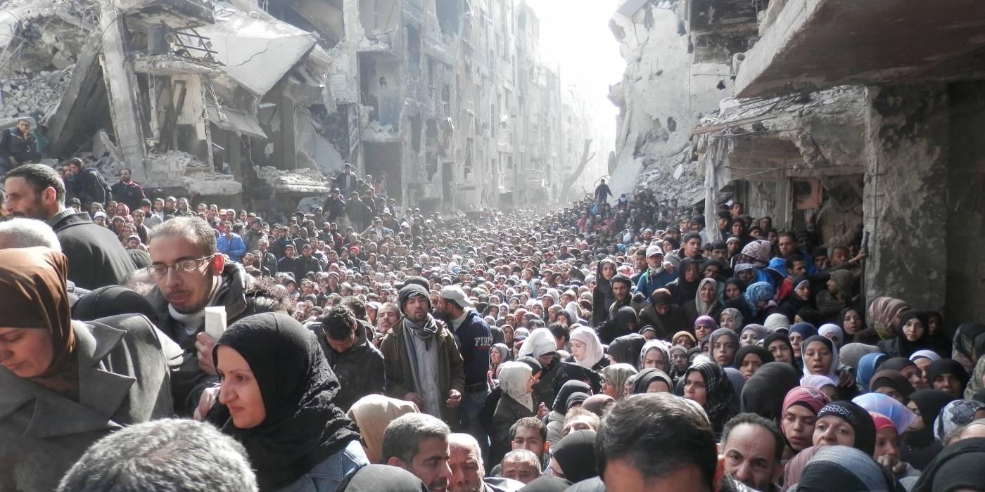I det palestinska flyktinglägret Yarmouk i Damaskus har tillgången till mat varit väldigt begränsat under kriget. Befolkningen står i kö för att få mat från FN. (Januari 2014). Foto: Zuma Press/UNRWA