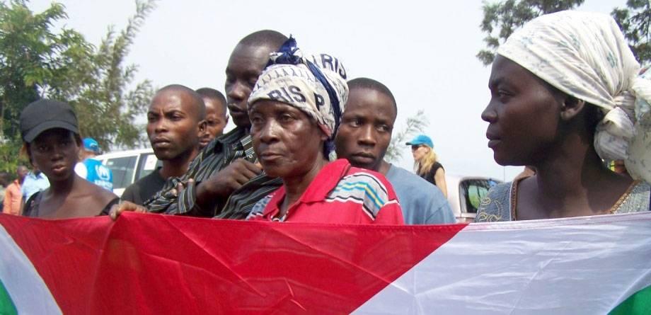 En grupp flyktingar som återvänder till Burundi från DR Kongo håller landets flagga medan de lyssnar på ett välkomsttal vid gränsen. Foto: IRIN/Judith Batusama