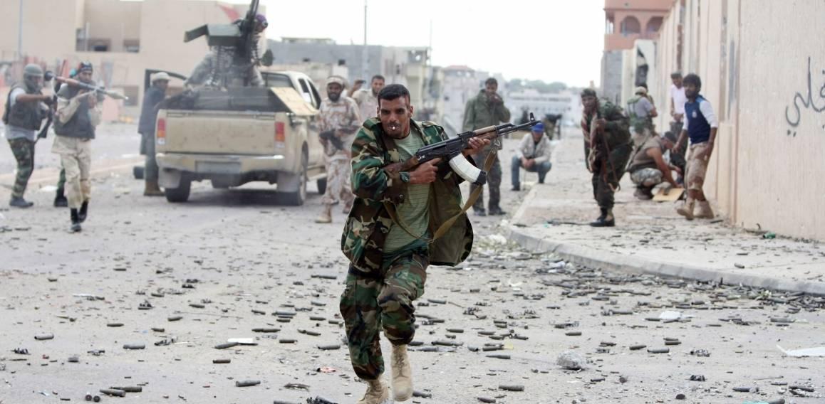 En soldat løper i dekning under kampen om byen Sirte i slutten av Gaddafis tid ved makten, 19. oktober 2011. Foto: NTB Scanpix/AFP photo/Ahmad al-Rubaye