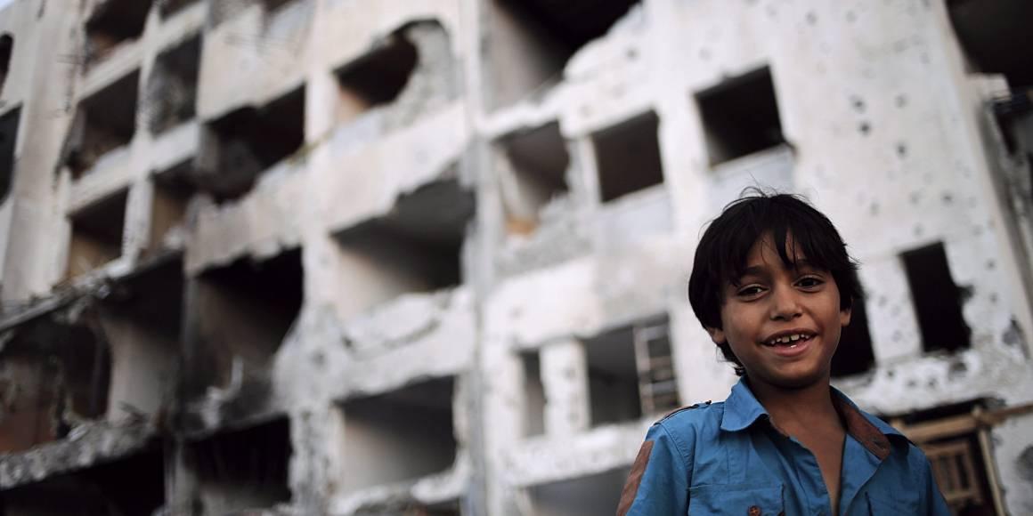 En palestinsk gutt står utenfor et hus som har blitt ødelagt av israelske bomber i byen Beit Lahiya på Gazastripen. Foto: EPA/Mohammed Saber