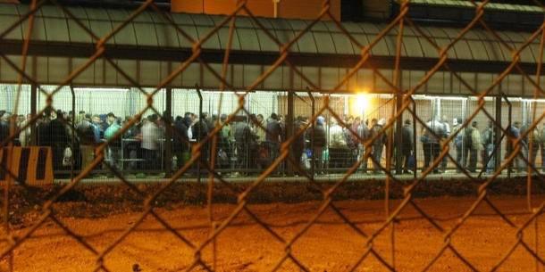 På billedet ses palæstinensere, der har fået tilladelse til at arbejde i Israel, og som står i kø for at komme igennem checkpoint i Qalqilia