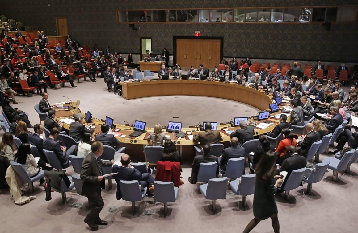 En mängd delegater sitter samlade runt ett bord format som en hästsko, de flesta med en laptop framför sig.