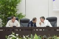 Tre män sitter i skrivbordsstolar vid ett bord. De två längst till höger är vända och framåtlutade mot varandra, till synes upptagna i ett samtal. Mannen längst till vänster tittar mot dem.