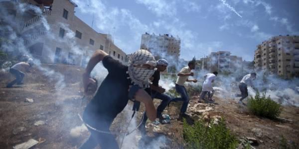 Palestinere demonstrerer mot krigen på Gaza i august 2014, og blir møtt med tåregass. Foto: AP/Majdi Mohammed