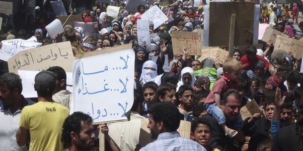 """Las personas Samler tenaces en Nawa bye, nær Deraa en abril de 2011, en uno de los demonstrasjonene første contra Regimet.  En skiltet dice """"Ikke noe won, medisin ikke noe, ikke noe alimentos.""""  Foto: REUTERS / Handout"""